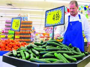 Roy Kirby stacks a bin of fresh cucumbers at the South Tucson Food City. Most of the produce at the grocery store comes from California or Mexico every morning. (Photo by Cecelia Marshall)